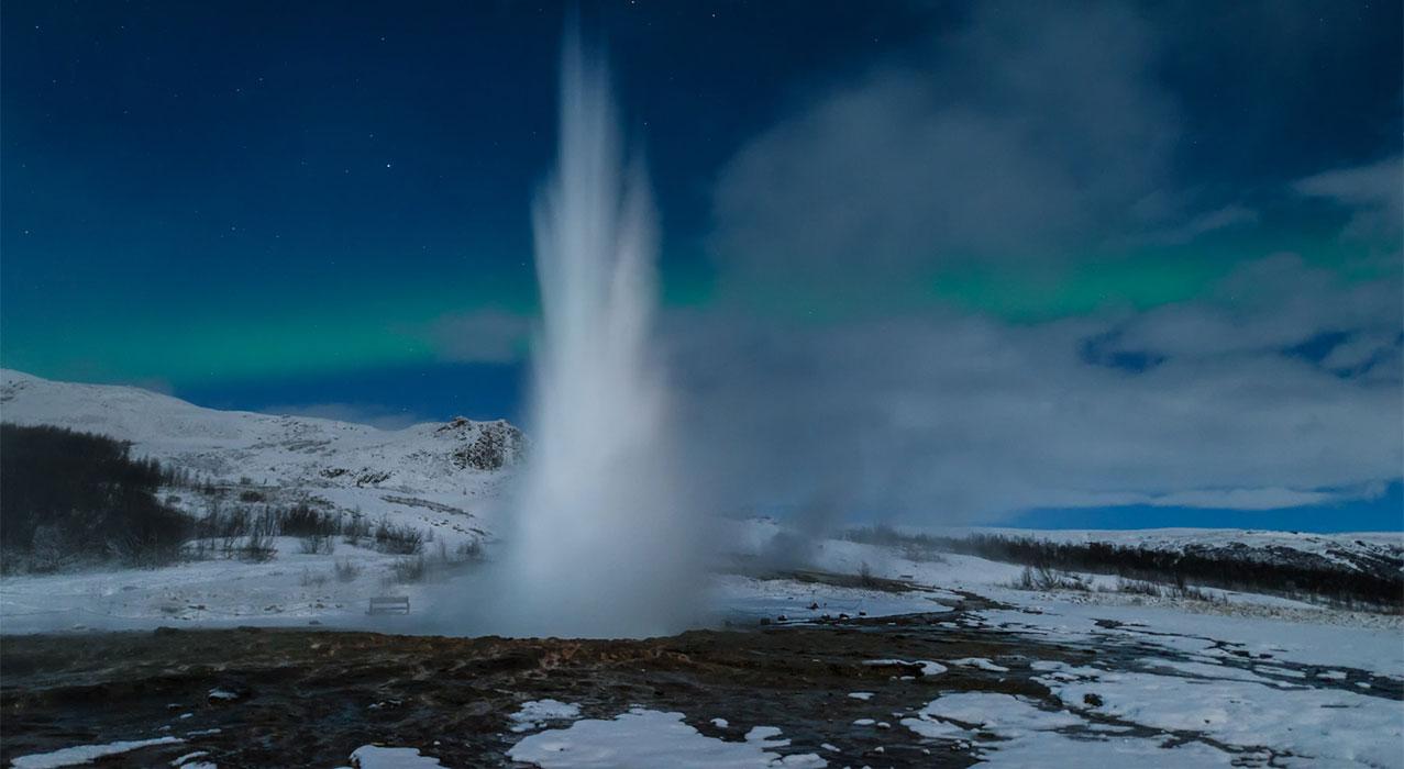 Der Geysir mit Nordlichter im Hintergrund.  Bild: Freiraum Fotografie
